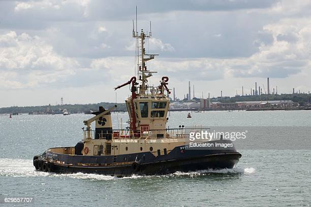 Tug Svitzer Sarah with a backdrop of Fawley Terminal on Southampton Water England UK