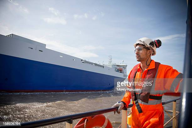 Tug worker looking out to sea as tug passes ship