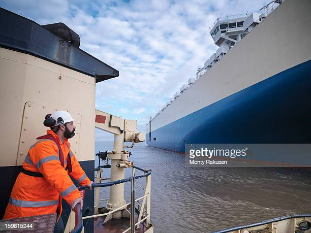 Tug worker wearing hard hat looking at ship