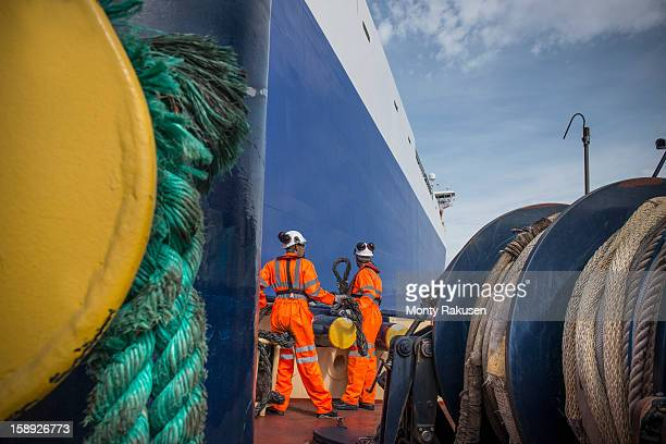 Tug workers on tug at sea with ropes in foreground