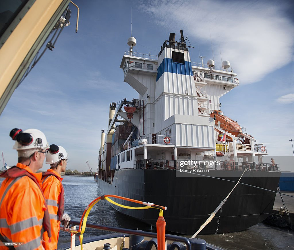 Tug Workers On Tug With Container Ship Close By Stockfoto