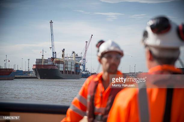 Tug workers on tug with container ship in background
