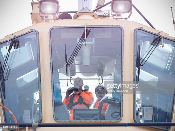 Tug workers wearing protective clothing looking through binoculars on tug