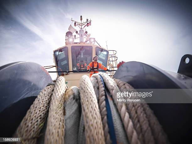 Tug workers wearing protective clothing on tug, rope in foreground