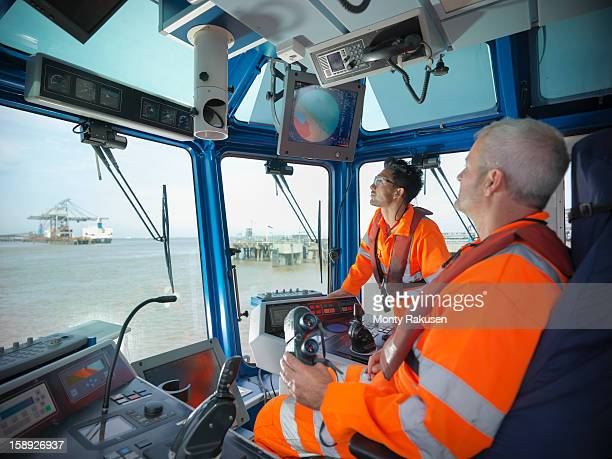 Tug workers wearing protective clothing steering tug