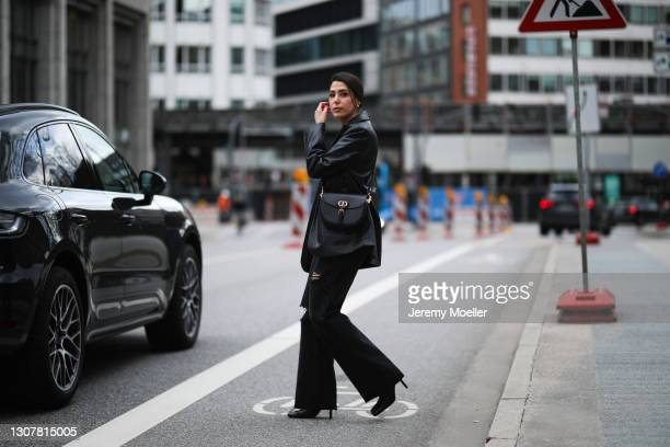 Tugba Kement wearing black NA-KD leather blazer, orange Zara top, black pants and boots and black Dior leather Bobby bag on March 17, 2021 in...