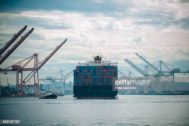 tugboat and container ship in industrial harbor - barge stock photos and pictures