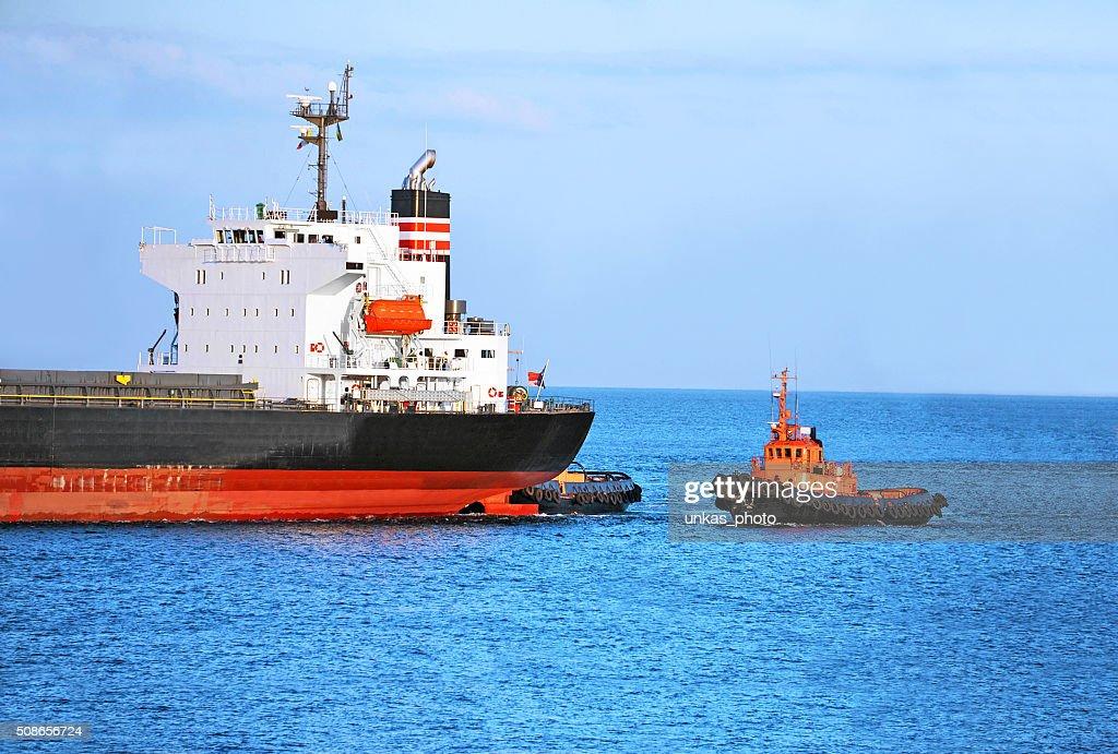 Tugboat assisting cargo ship : Stock Photo