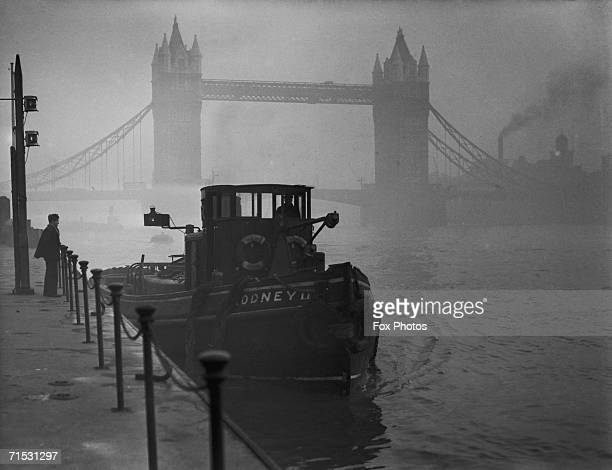 A tugboat on the Thames near Tower Bridge in heavy smog 1952