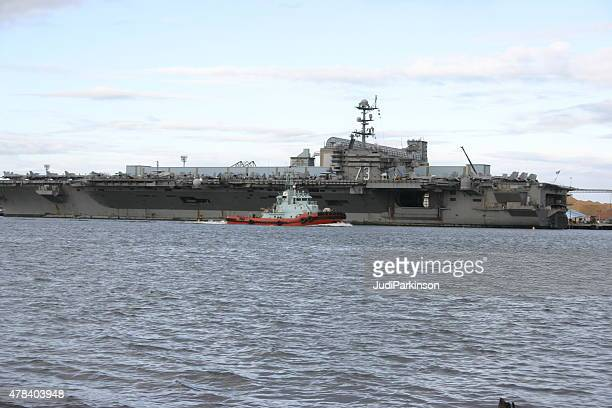 tugboat passing uss george washington docked at port of brisbane - uss george washington stock photos and pictures