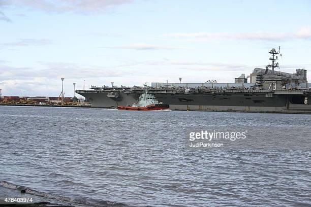 Tugboat Passing USS George Washington Docked at Port of Brisbane