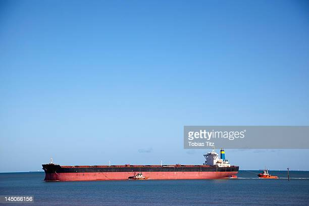 a tugboat pulling a freight ship - barge stock photos and pictures