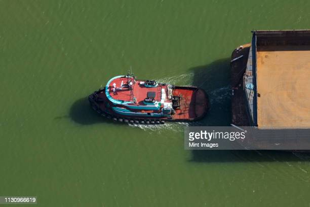 tugboat pulling barge - tugboat stock photos and pictures