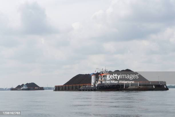 tugboat pulling coal barge ship in balikpapan bay, indonesia - kalimantan stock pictures, royalty-free photos & images