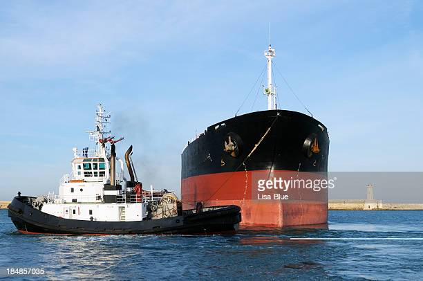 tugboat pulling industrial ship - tugboat stock photos and pictures