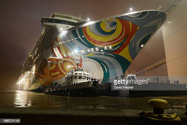 A tugboat pulls the Norwegian Getaway cruise ship down the Ems river towards the North Sea shortly after construction of the ship was finished at the...