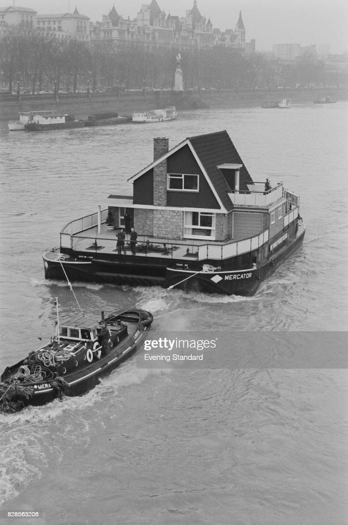A tugboat pulls the Sunley House, a two-storey house built on a