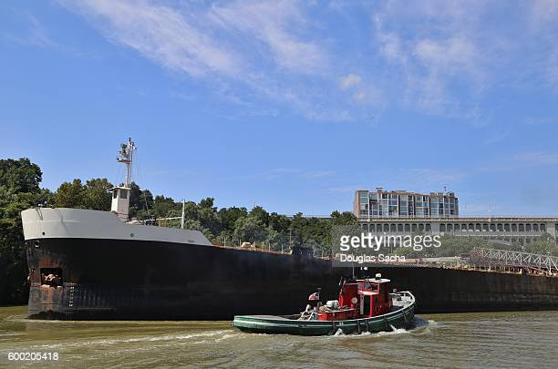 Tugboat pushes a Cargo ship through a narrow waterway