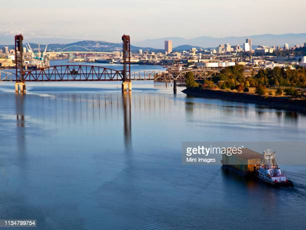 tugboat pushing barge in river - willamette river stock photos and pictures