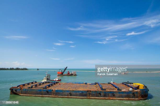 tugboat pushing barge - barge stock photos and pictures