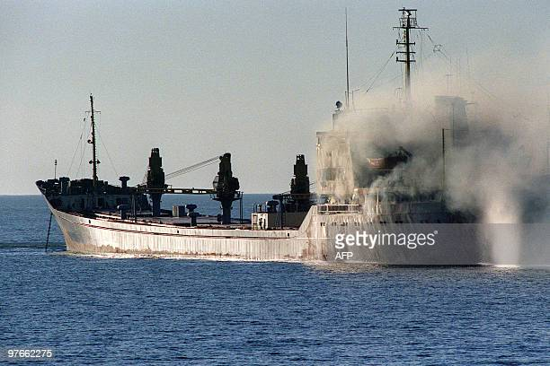A tugboat puts out a fire November 23 on the 8750 ton Romanian flagged freighter Fundulea which was hit by an Iranian warship causing severe damage...