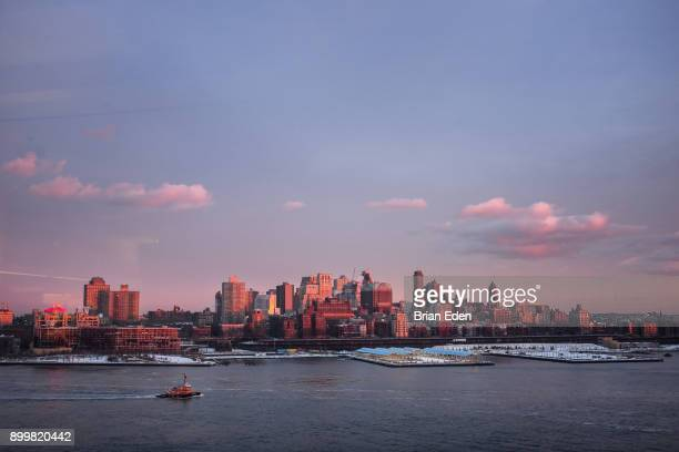 A tugboat sails across the East River in front of the Brooklyn skyline at sunset