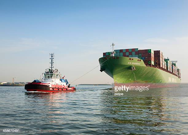 tugboat towing cargo container ship - tugboat stock photos and pictures