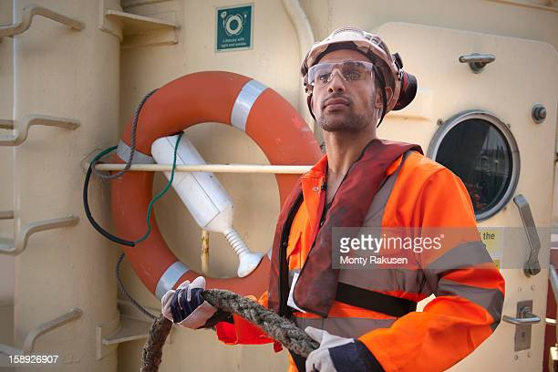 Tugboat worker holding thick rope and wearing protective clothing
