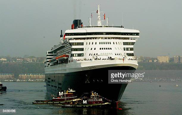 Tugboats escort the Queen Mary 2 the world's largest cruise ship as it pulls into port April 22 2004 in New York City The new flagship of the Cunard...