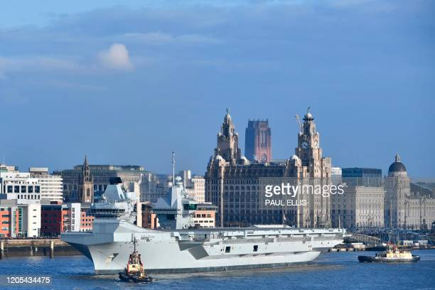 Tugboats manoeuvre Britain's Royal Navy's HMS Prince of Wales, as it prepares to leave the docks in Liverpool, north west England on March 6, 2020.