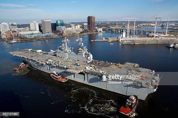 tugboats position the amphibious assault ship uss kearsarge. - norfolk virginia stock photos and pictures