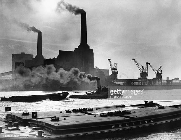 Tugs and barges on the water by Battersea Power Station in Battersea London England UK