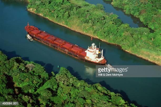 Tugs guiding cargo ship through Panama Canal, aerial view, Panama