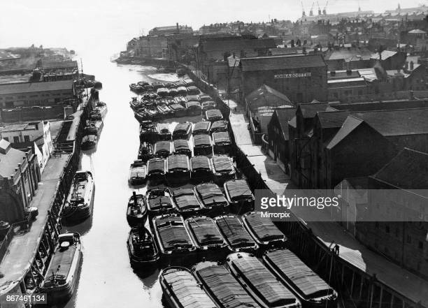 Tugs lighters and barges moored to the staithes awaiting to unload their goods into warehouses along the River Hull Whilst others wait to continue...