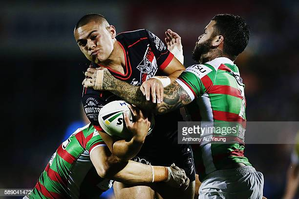 Tuimoala Lolohea of the Warriors charges into Adam Reynolds and Kyle Turner of the Rabbitohs during the round 23 NRL match between the New Zealand...