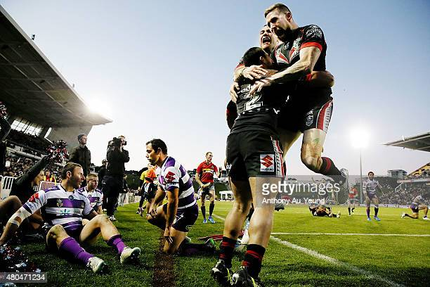 Tuimoala Lolohea of the Warriors is congratulated by teammates Sam Tomkins and Bodene Thompson after scoring a try during the round 18 NRL match...