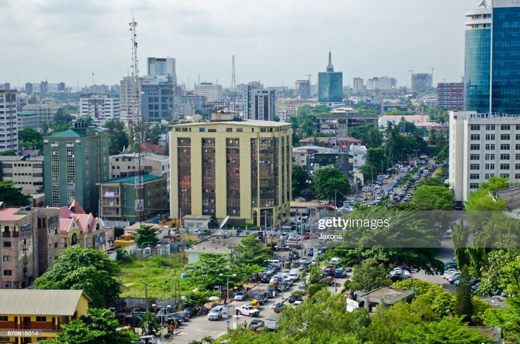 Tuk tuk drivers and other road users travel around the port city of Lagos : Stock Photo