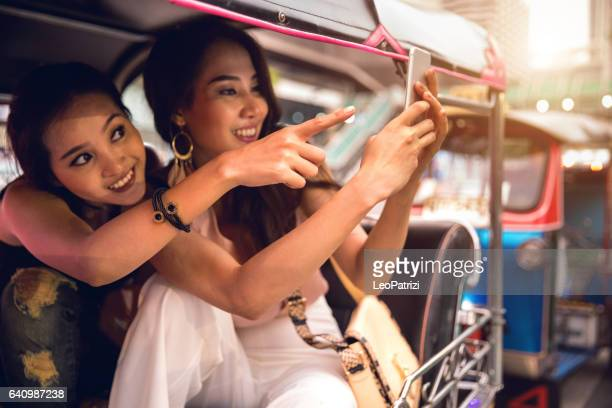 Tuk Tuk ride, Women on board discovering Bangkok, Thailand