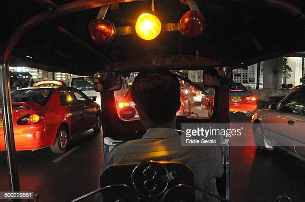 Tuk tuk taxi driver riding in traffic jam at night in Bangkok Thailand