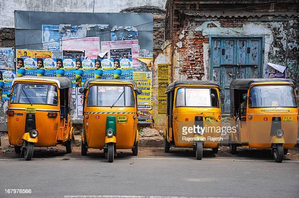 Tuk Tuk's or the Auto Rickshaws parked infront of a run down shop along Mahatma Ghandi Road, Puducherry , India. Inside the auto rickshaws are the...