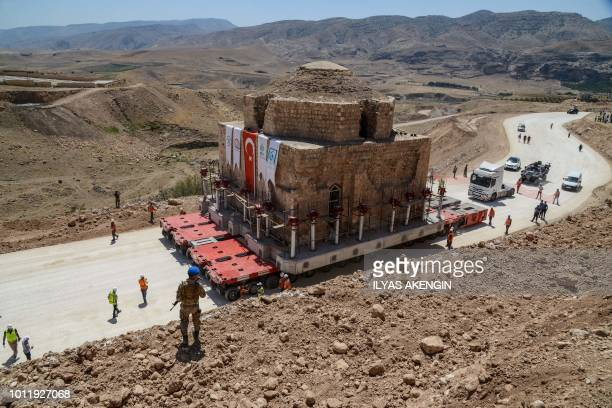 A Tukish soldier stands guard as the Artuklu Hamam a centuriesold bath house weighing 1600 tonnes is loaded onto a wheeled platform and moved down a...
