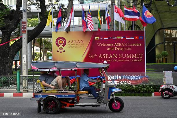A tuktuk driver transports his passengers passing by a billboard for the 34th Association of Southeast Asian Nations summit in Bangkok on June 21 2019