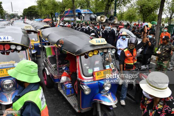 Tuk-tuk drivers and motorbike taxi drivers hold up the three-finger salute as they arrive to show their support for anti-government protesters...