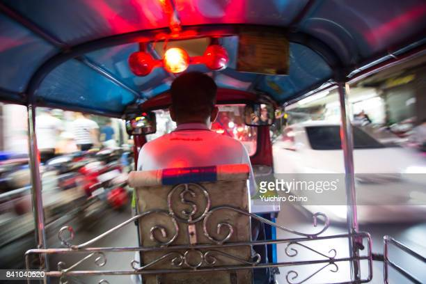 tuk-tuk in motion in bangkok at night - human powered vehicle stock photos and pictures