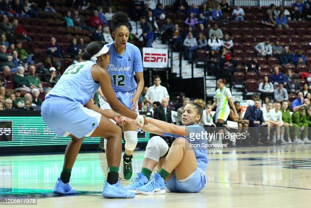 Tulane Green Wave forward Krystal Freeman assists Tulane Green Wave guard Dynah Jones from the floor during the women's American Athletic Conference...
