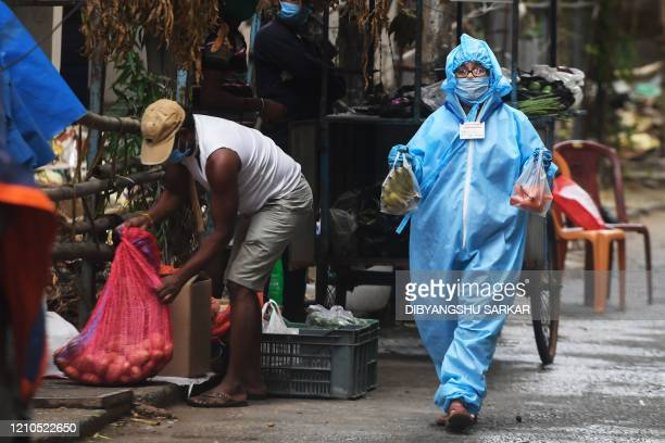 TOPSHOT Tulika Roy a municipal worker walks to deliver vegetables from a vendor for residents of a restricted area with COVID 19 positive cases...