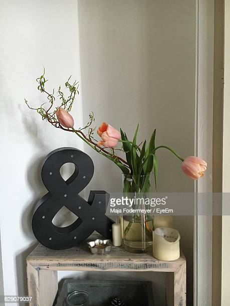Tulips In Vase By Ampersand On Table Against Wall At Home