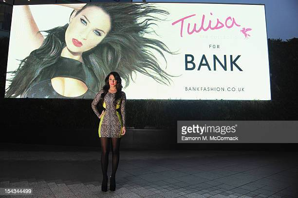 Tulisa Contostavlos poses in front of a billboard promoting her TFB by Tulisa for Bank debut clothing range during the TFB by Tulisa for Bank launch...