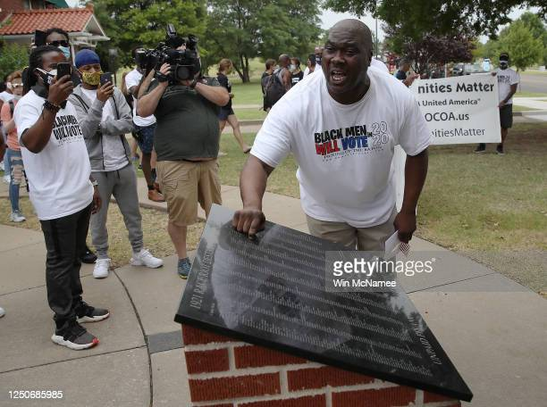 Tulsa resident Bruce Carter pounds on a plaque in front of the 1921 Black Wall Street Memorial during a Juneteenth celebration in the Greenwood...