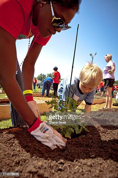 Tulsa Shock player Tiffany Jackson helps Conner Quick plant a tomato plant at Wright Elementary school on May 21 2011 in Tulsa Oklahoma during a WNBA...